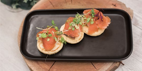Blinis with smoked salmon, dill caper cream cheese and micro herbs