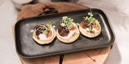 Blinis with red onion confit, crème fraîche & chives (v)