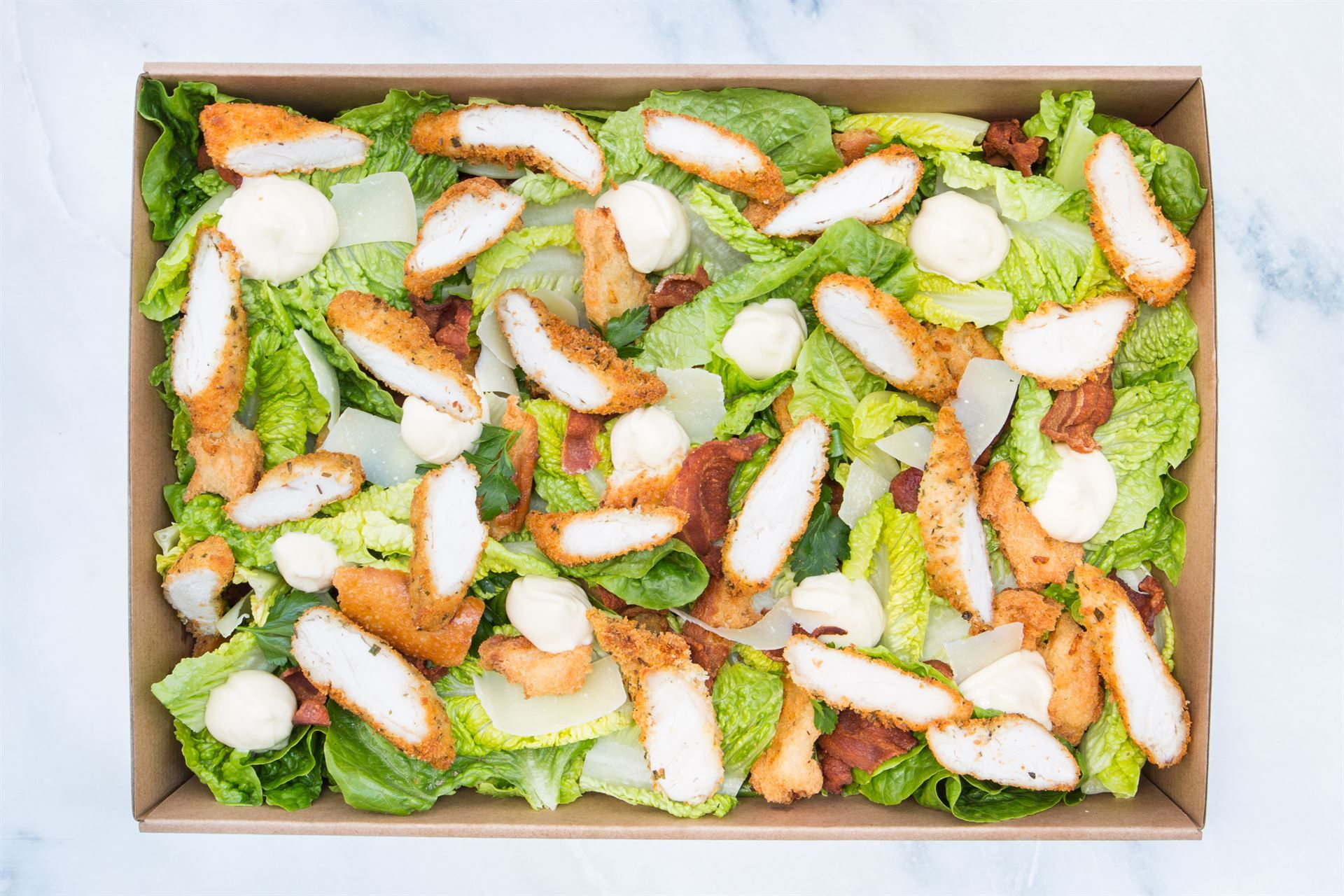 Crispy crumbed chicken caesar salad: cos hearts, sourdough croutons, bacon, egg, & parmesan